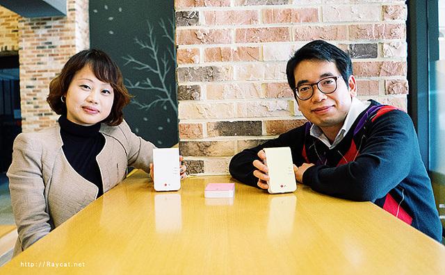 포켓포토를 기획한 유하나, 김영철 과장이 각 각 손에 2014년형 포켓포토 한 대 씩을 들고 카메라를 향해 미소짓고 있다.