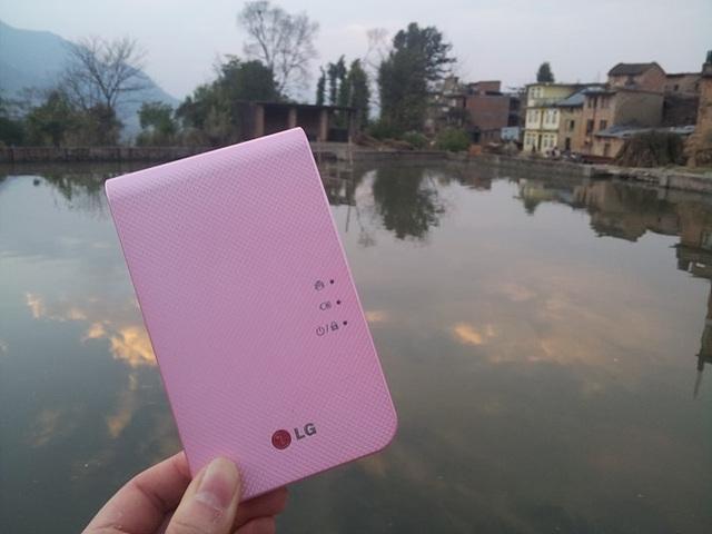 배경으로 네팔의 호수가 보이고 멀리 집과 나무들이 보인다. 2014년 포켓포토 분홍색 제품이 앞쪽에 크게 보인다.