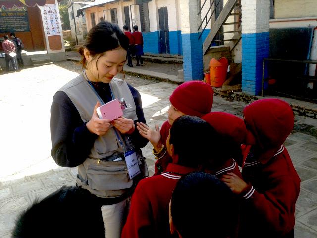 봉사단원이 포켓포토를 들고 아이들을 쳐다보고 있으며 아이들이 봉사단원 주변에 모여 있다.