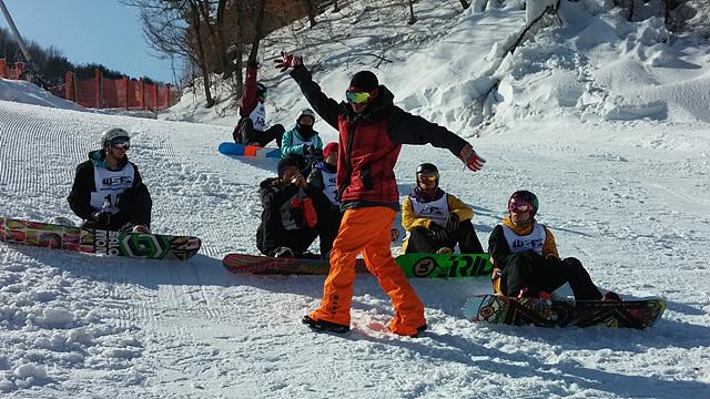WSF 활동을 하는 사람들이 스키장 위에 앉아 설명을 듣고 있다.