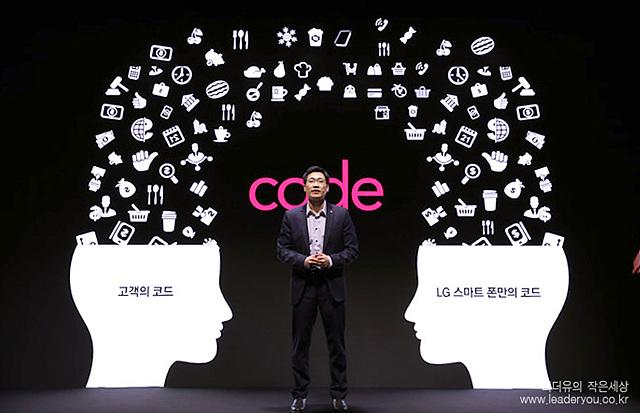 코드를 설명하고 있는 모습이다. 남자가 중앙에 서있고 양 옆으로 고객의 코드와 LG스카트 폰안의 코드라는 글귀가 적혀있다. 좌, 우측에 사람의 뇌에서 다양한 아이콘들이 쏟아져나오고 있다.