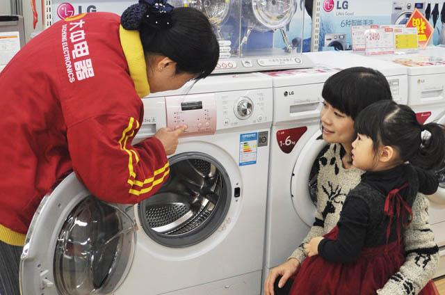 중국 베이징의 가전 매장을 찾은 고객들이 LG 미니 드럼세탁기 '꼬망스' 제품을 살펴보고 있다.