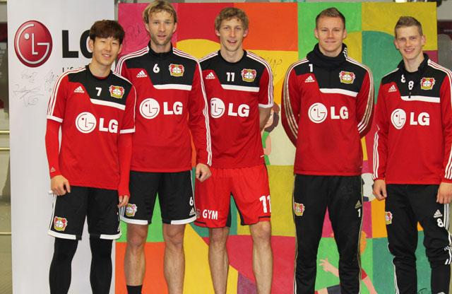 손흥민 선수를 비롯한 레버쿠젠 선수들이 그림 앞에서 기념촬영을 하고 있다.