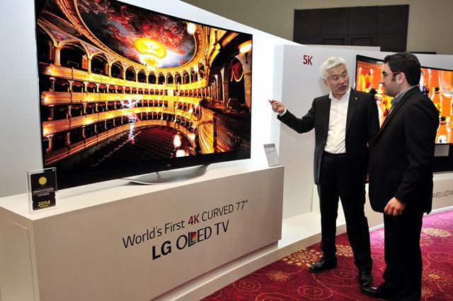 LG전자 중아지역대표 차국환 전무(왼쪽)가 주요 거래선에게 77형 울트라HD 곡면 올레드 TV를 소개하고 있다.