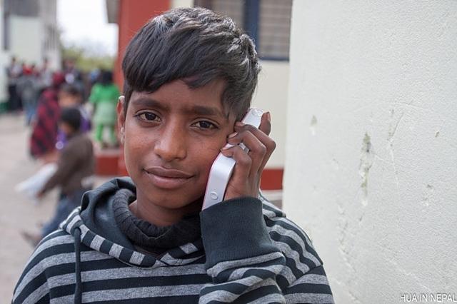 네팔 남학생이 포켓포토를 한 손에 들고 귀에 가까이 대어 사진이 나오고 있는 소리를 듣고 있다.