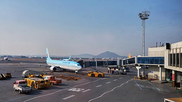 여행을 출발하기 전에 G플렉스로 비행기를 촬영한 모습이다. 비행기 주변에는 여러 화물차들이 주차되어 있다.