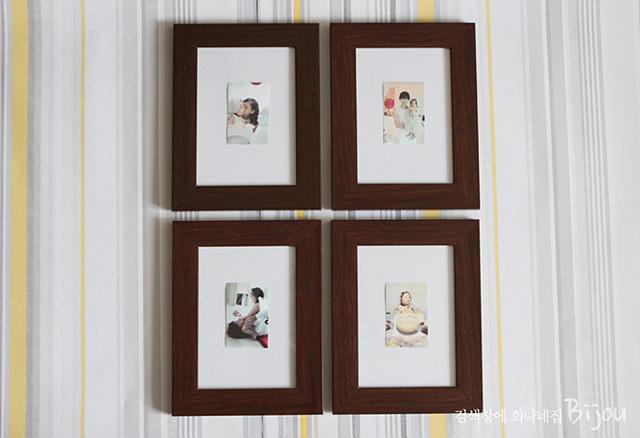 한 쪽 벽면에 짙은 브라운 벽걸이 액자를 걸어 놓은 모습이다. 각 액자 안에는 포켓포토로 인화한 사진이 들어가 있다.