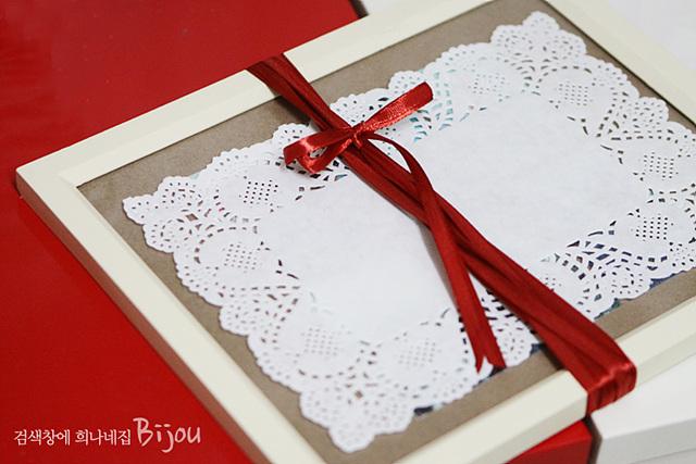 액자를 빨간 끈을 이용해 포장한 모습이다.