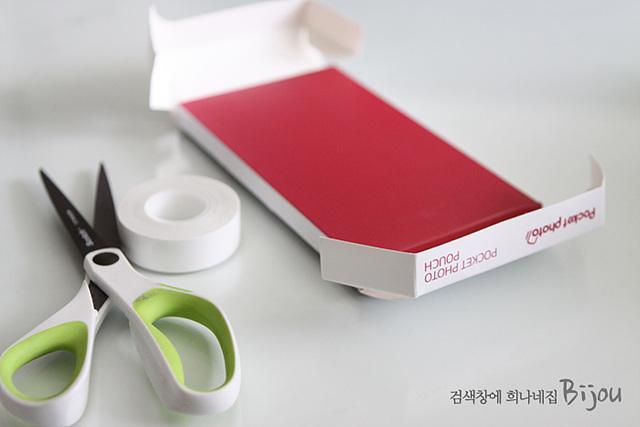 포켓포토 케이스 겉의 종이 박스와 가위, 양면 테잎이 놓여져 있다.