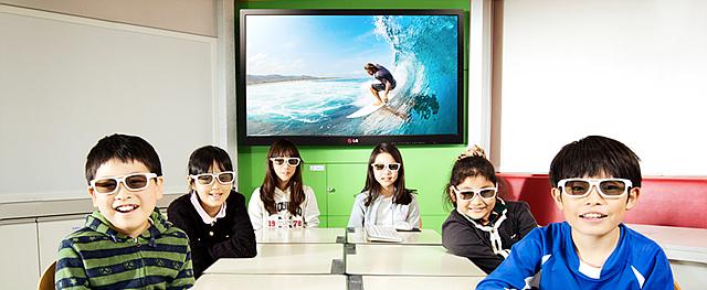 초등학생들이 티브이를 등지고 3D안경을 끼고 미소를 짓고 있다