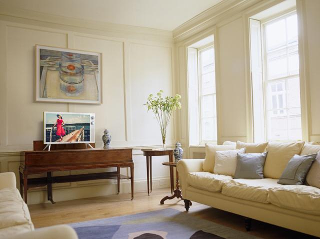 환하고 편안한 분위기의 아이보리톤 집안 풍경, 폭신한 침대와 넓은 유리창으로 들어오는 햇빛이 아늑하다. 클래식 TV가 멋스럽게 액자 밑에 놓여져 있다