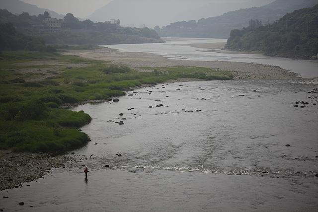 흐린 날 섬진강의 전경.한 낚시꾼이 낚시를 즐기고 있다
