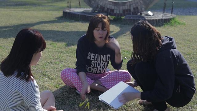 편안한 차림으로 잔디밭에 앉아 콘티에 대해 토론중인 여대생들의 모습이다