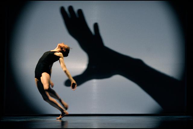 """""""솜브레로""""의 한 장면으로 여자 무용수가 몸을 활처럼 둥글게 만들고 무대 벽쪽에 커다란 손이 그녀를 잡아당기고 있는 모습이다"""
