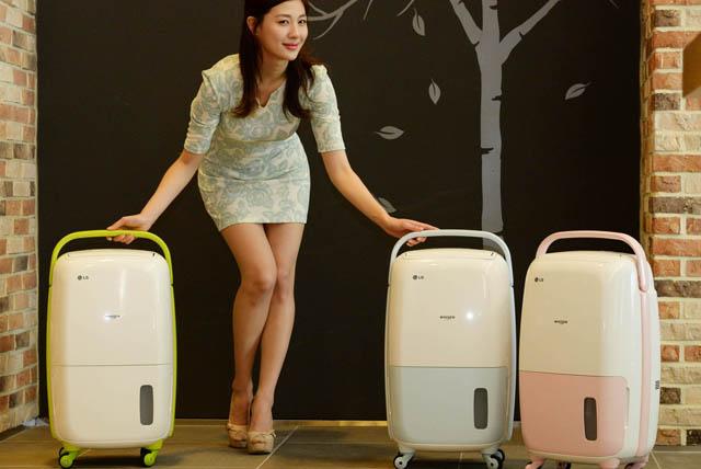여성 모델이 여행가방처럼 이동 편의성과 디자인을 강화한 LG 휘센 제습기 신제품을 소개하고 있습니다.