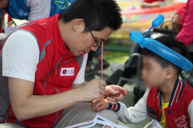 파란 풍선 머리띠를 한 아이의 손에 엘지 임직원이 페이스 페인팅을 해주고 있다