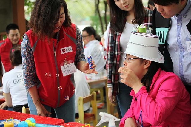 엘지 임직원이 하얀 모자를 쓴 분이 비누방울을 불어 볼 수 있도록 도와주고 있는 모습이다