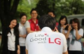 Life's Good With LG' 라고 쓰여진 흰 티셔츠사내가 사람들의 단체사진을 찍어주고 있다