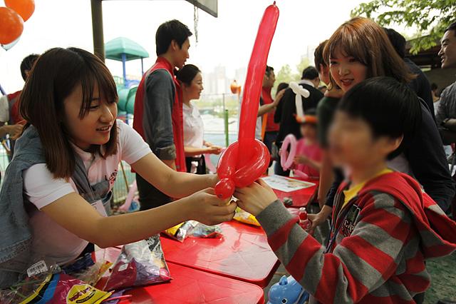 러브지니 윤재경 학생이 아이에게 빨간풍선으로 만든 칼자루를 쥐어주고있는 모습이다