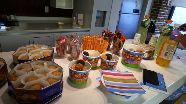 테이블 위에 쿠키, 소시지, 음료 등 다과가 준비되어 있다