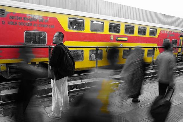 열차를 기다리는 길잡이 아저씨. 빨간색과 노란색의 열차 외에는 흑백으로 보인다.