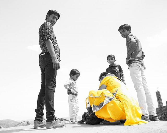 인도 가족이 카메라를 응시하고 있다. 노란색 옷을 입은 한 여성 외 모두 흑백의 모습