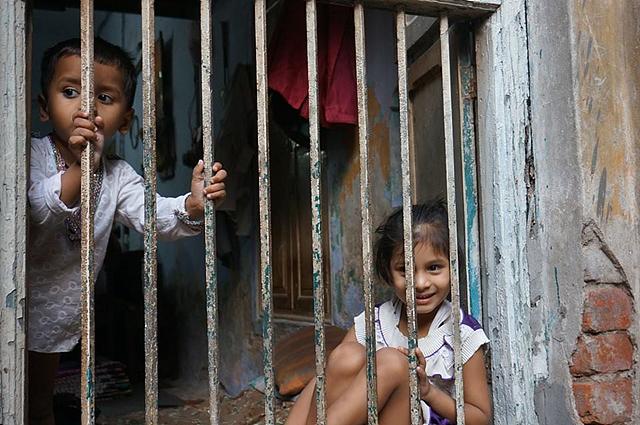 인도 아이 두명이 철조망 안에서 미소를 짓고 있다