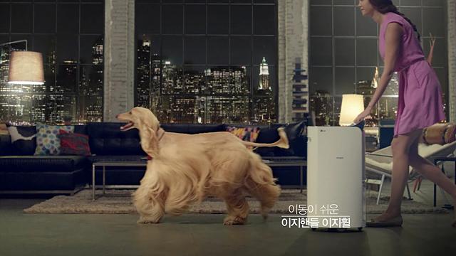 2014_휘센_제습기_광고_이동이 쉬운 이지핸들 이지휠. 제습기를 손으로 잡은 채 강아지를 따라가는 한 여성의 모습