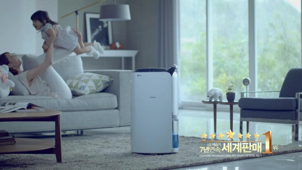 2014 휘센 제습기 광고 스틸 컷. 거실 한가운데 놓인 제습기 뒤로 아이와 함께 노는 엄마의 모습이 보인다.