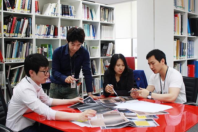 제품 디자인팀원들이 테이블에 앉아 회의를 하고 있는 모습이다