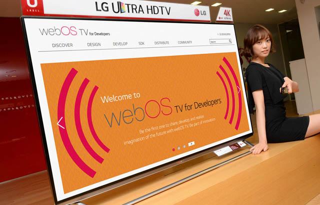 웹OS 스마트+ TV와 포즈를 취하고 있는 모델 모습 입니다.