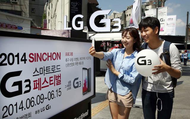 신촌 연세로 내에 설치된 'LG G3' 체험존 앞에서 일반인 커플들이 'G3'로 사진 촬영을 하면서 즐거워 하고 있는 모습 입니다.