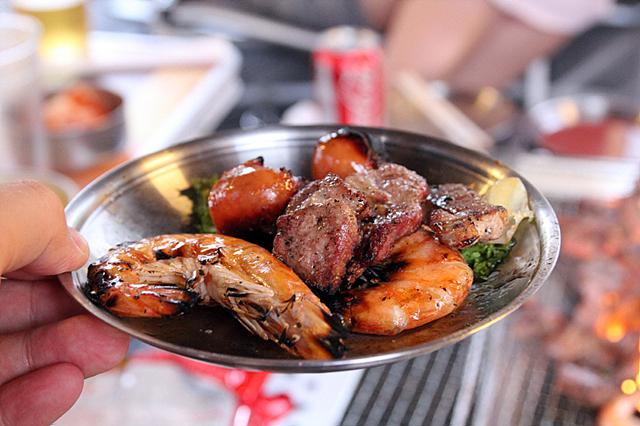 그릇에 노릇하게 구워진 고기와 새우 소시지 등이 올라가 있다