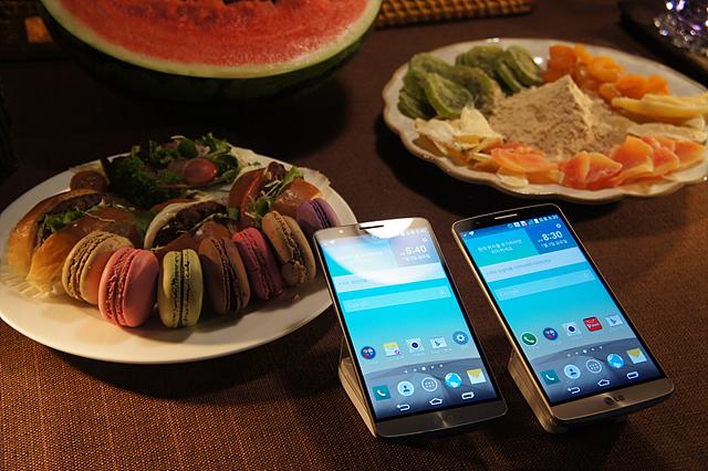 어두운곳에서 빛을 발하는 G3 카메라. 테이블에 놓인 두 대의 G3 휴대폰 뒤로 마카롱 등 다과의 모습이 보인다.