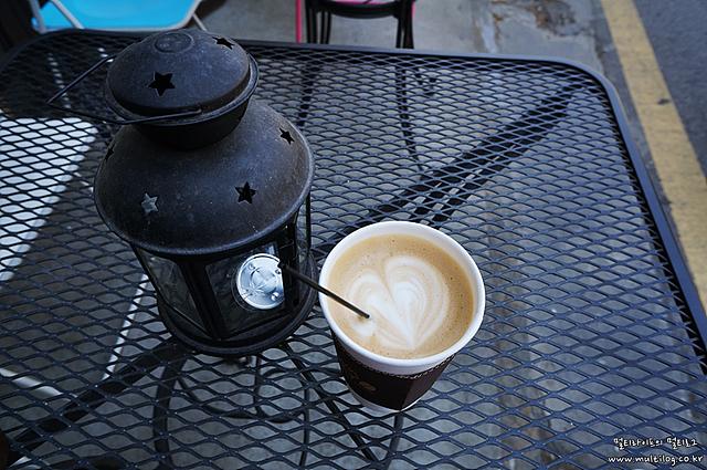테이블에 올려져 있는 램프와 종이컵에 담긴 따뜻한 커피