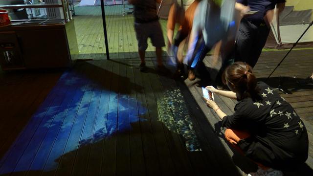 더블로거들이 미니빔 TV로 바닥에 쏘아진 이미지를 활용해서 영상을 만들고 있는 모습이다