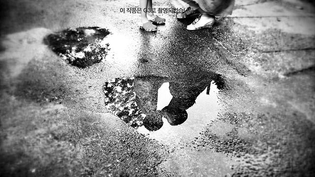 마와 아이가 입을 맞추고 있는 모습이 빗물에 비치고 있다. 흑백사진