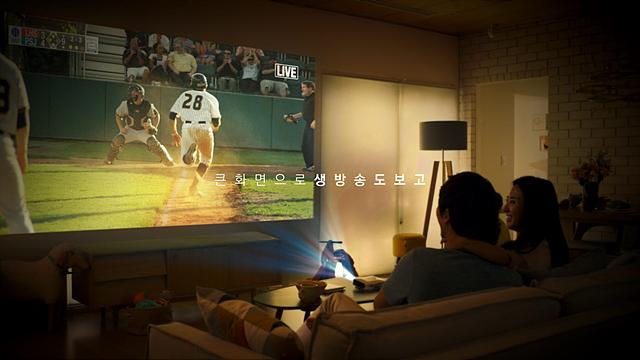 집 안에서 미니빔 TV로 송출된 야구경기를 즐기는 모습