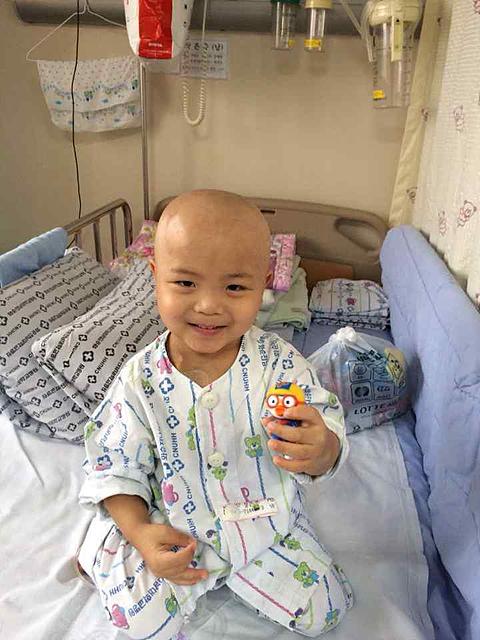 병실 침대에 앉아있는 하랑이가 장난감을 손에 들고 밝은 미소를 짓고 있다