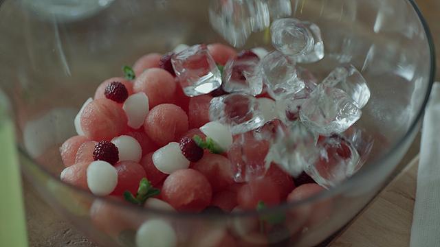 동글게 잘라진 수박이 담긴 그릇에 얼음을 쏟는 모습