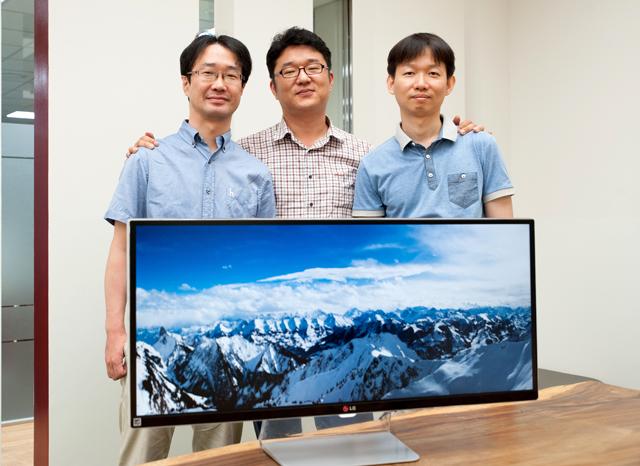 씨네뷰 모니터 개발자들이 만년설이 덮인 산 이미지가 띄워져있는 모니터 뒤에서서 미소를 짓고있다
