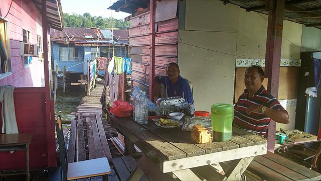 친절한 브루나이의 사람들. 두 명의 브루나이 남성이 테라스 테이블에 앉아 음식을 권하고 있다.