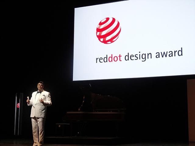 레드닷 디자인 어워드 시상식 현장. 흰 색의 정장을 입은 사회자의 모습.