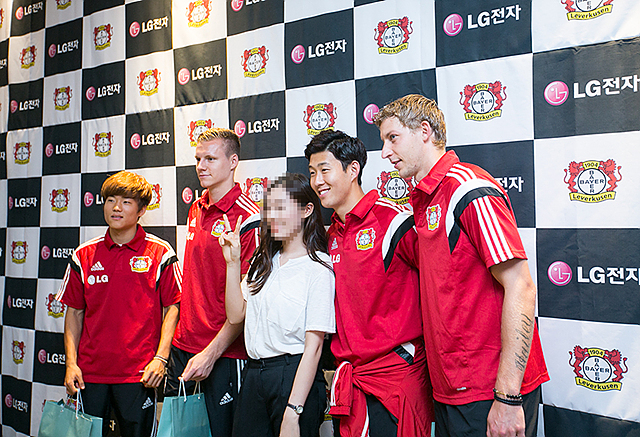 4명의 레버쿠젠 선수들과 포토월 앞에서 기념 촬영하는 여성 팬