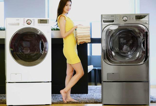 모델이 트롬 드럼세탁기 신제품 2종과 함께 환하게 웃으며 포즈를 취하고 있습니다.