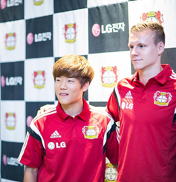 붉은 색 유니폼을 입은 류승우 선수의 모습. 다른 외국인 선수와 어깨동무를 하고 있다.