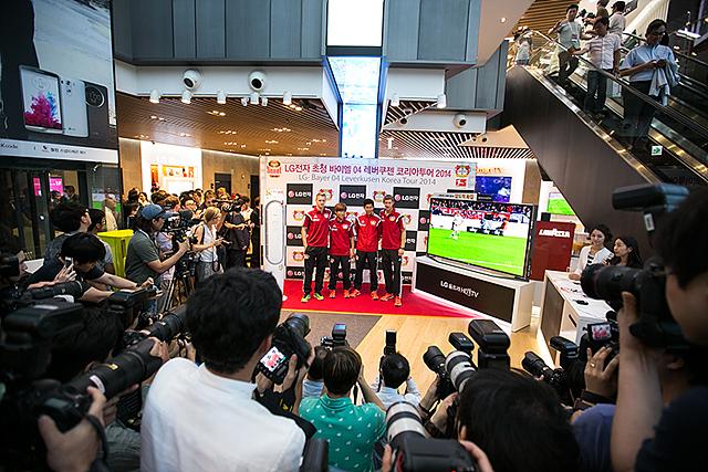 베스트샵에 모인 레버쿠젠 선수들이 포토월 앞에 서있다. 잔뜩 모인 사람들과 기자들이 촬영하고 있는 모습