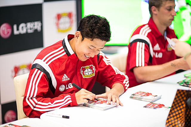 손흥민 선수가 미소를 지으며 싸인을 해주고 있다.