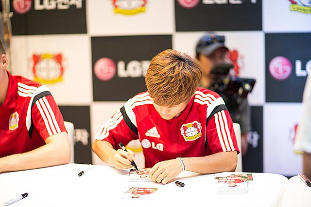 류승우 선수 가 자신의 사진에 싸인을 해주고 있다.