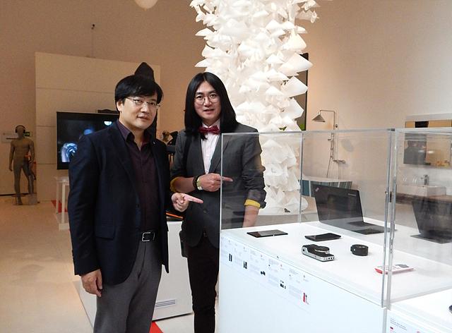 곡면 스마트폰 G-Flex와 기념촬영하고 있는 LG전자 남자 직원 두 명의 모습